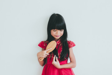 A cute asian kid girl wearing red Chinese dress and comb her beautiful long silky black hair