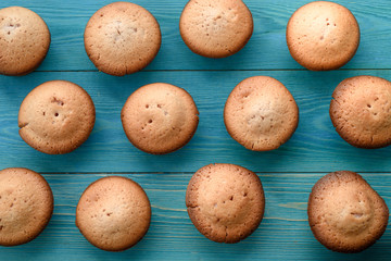 Fresh muffins on a cutting board on a wooden blue background. Background..Texture of freshly baked muffin. Close-up. Macro