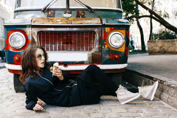 Woman lies with ice-cream before an old bus