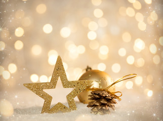 Christmas Holiday Scene with Bauble, star en Fire Cone on Snow against Blurred Bokeh Light Background with Copy Space