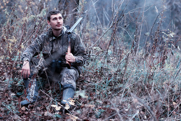 A man in camouflage and with a hunting rifle in a forest on a spring hunt