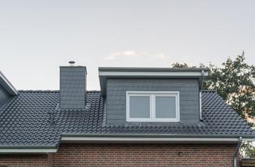 Dach eines Hauses mit Schornstein und Gaube