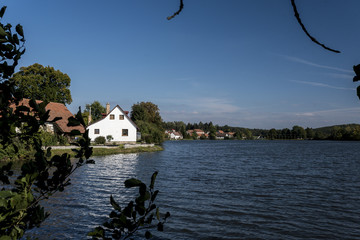 and a white house in a small village on the banks of the Moravian Pond