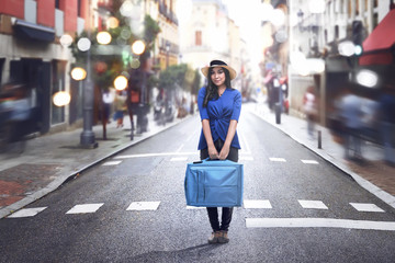 Smiling asian woman wearing hat and holding suitcase
