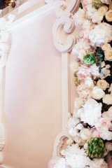 Pink flower garland made of roses and hydrangeas hangs on the wall