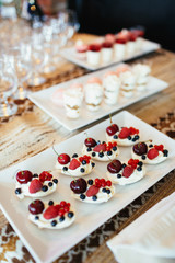 White cookies with berries served on white plate