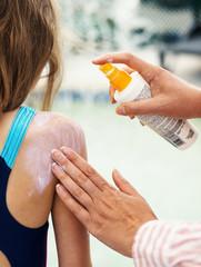 Woman's hand applying suntan cream on child back.