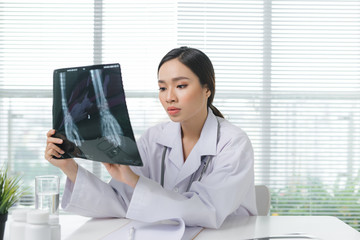 Woman doctor in hospital looking at x-ray film healthcare