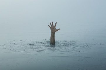 Danger, problems concept. Close up of human hand drowning in the lake Fototapete