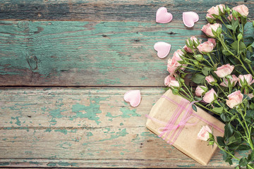 Background with a bouquet of pink roses and a gift box on old blue boards. Space for text.