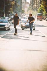 Two pro skateboard rider ride skate through cars on street