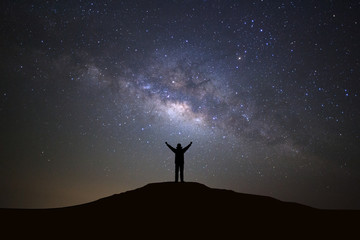 Landscape with milky way galaxy, Starry night sky with stars and silhouette of a standing sporty man with raised up arms on high mountain.