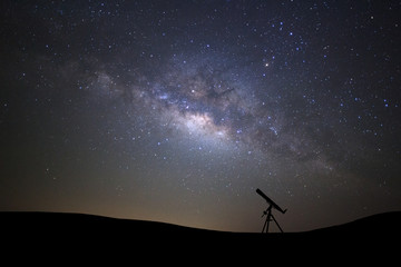 Silhouette of telescope watching the wilky way galaxy with stars and space dust in the universe