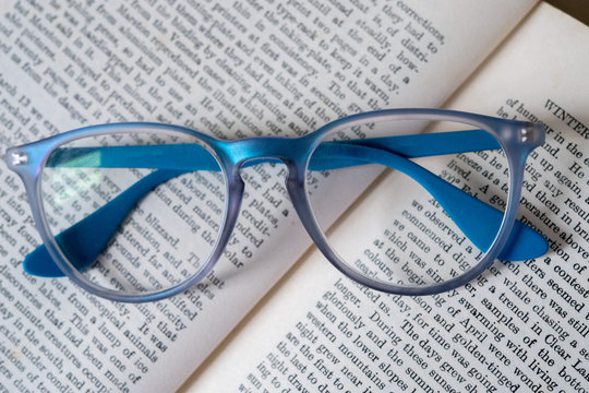 light blue reading glasses isolated on a book
