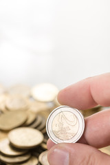 Two metal euro coins in the hand with white copy space background