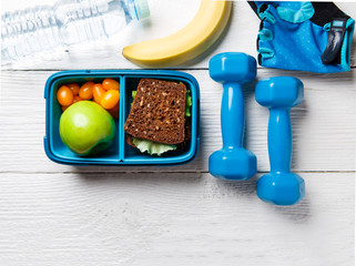Photo on top of apple, sandwich, tomato in box, dumbbell