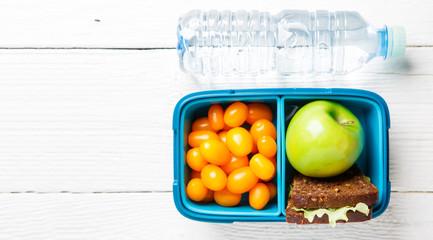 Photo of cherry tomato, apple, sandwich in lunchbox, bottle