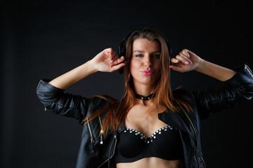 Studio image of young model in headphones with hands at head
