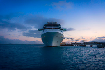 Water level view of cruise ship bow, docked at sunset, bermuda
