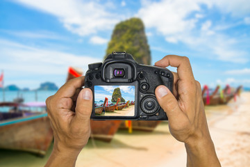 Hands holding camera and take photograph of beautiful beach at Railay Beach in Thailand