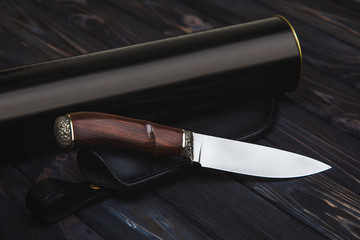 Hunting knife with wooden handle and leather case isolated on white