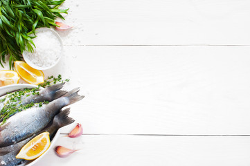 White wooden background with fresh raw fish and ingredients