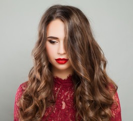 Beautiful Woman with Event Makeup and Long Healthy Wavy Hair. Portrait of Cute Young Model with Red Lips Makeup