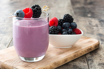 Healthy berry smoothie in glass on wooden table Fototapete