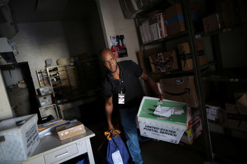 Juan Rivera, from the U.S. Postal Service, picks up the mail at an area affected by Hurricane Maria in the island of Culebra, Puerto Rico