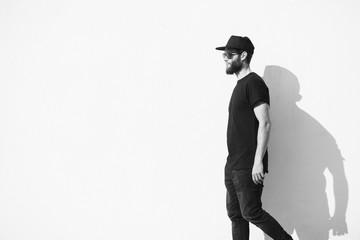 Hipster man walking along a wall wearing black clothes