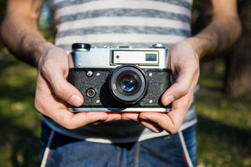 Young man holding in hands old vintage camera. Man photographer and film retro camera. Say cheese!