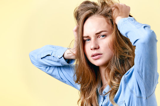 Young distraught redhead teenager with freckles pulling her hair. Tired stressed and depressed female student. Negative emotions, depression concept.
