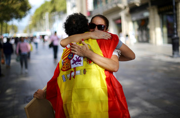 """A man wearing a Spanish flag gives """"free hugs"""" in central Barcelona"""