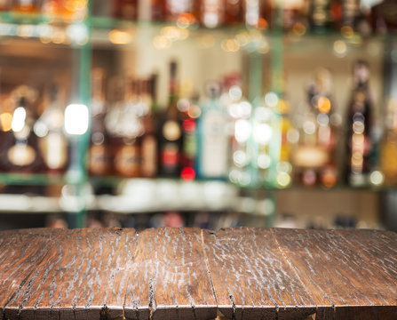 Wooden countertop and blurred bar shelves at the background.