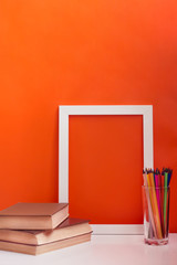 desk with white blank picture frame mock up. Рencils and books on orange background. Сoncept of teacher's day. Copy space