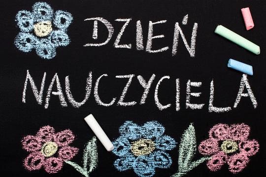 Szkolna tablica z napisem Dzień Nauczyciela, oraz narysowane kredą kolorowe kwiaty.