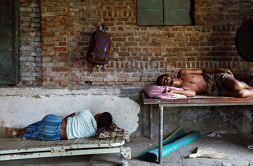 Workers rest inside a closed-down factory in an industrial area on the outskirts of Mumbai