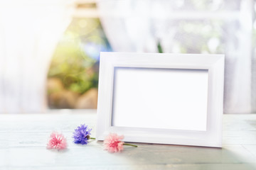 Empty white frame mockup and flowers