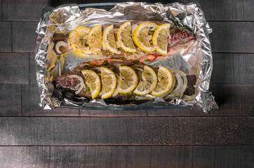 raw trout, fish with spices, herbs and lemon in a baking dish top view