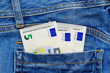 Small euro banknotes in jeans pocket