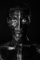 woman with black dirty smeared make up on black background, monochrome