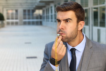 Mad businessman blowing a whistle