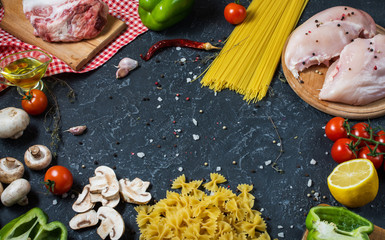 Pasta ingredients. Chicken breasts, Cherry tomatoes, spaghetti pasta, bacon and mushrooms on the stone table.