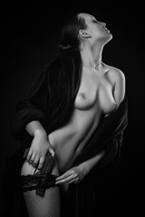 armed woman with beautiful naked body in bathrobe and stockings on dark background, monochrome