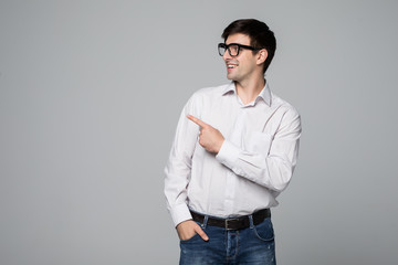 Handsome smiling man pointing away on gray background.