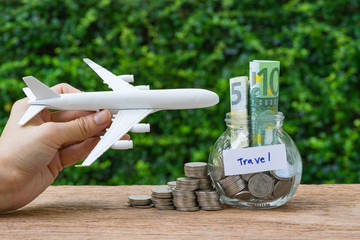 Hand holding miniature toy airplane with glass bottle jar with full of coins and banknote as saving for travel concept