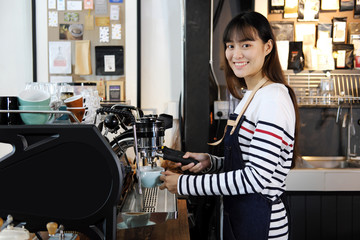 Smiling asian barista preparing cappuccino with coffee machine. Cafe restaurant service, Small business owner, food and drink industry concept.