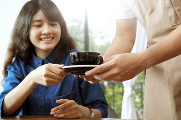 Close-up of a waitress serving a cup of coffee to young beautiful customer.