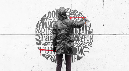 Street artist drawing various word with spraycan on wall