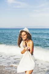 Attractive woman with white scarf and hat, enjoying the water and the sunlight on the beach